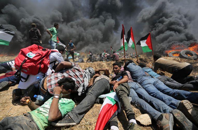 Palestijnse demonstranten kruipen bij elkaar tijdens de confrontatie met Israëlische veiligheidstroepen.  Beeld Photo News