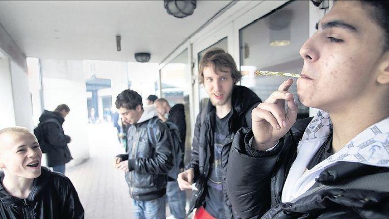 Jongeren in Amsterdam roken een joint. De grote steden keerden zich alle vier tegen de wietpas. Beeld Arie Kievit