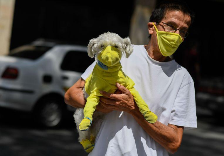 Een man draagt een mondkapje om zijn hond te beschermen tegen het virus.  Beeld AFP
