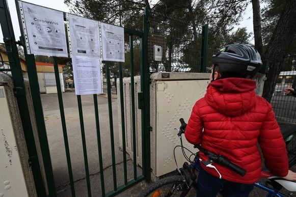 Een scholier staat voor een gesloten poort in het Franse Jacou, nabij Montpellier.