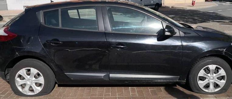De vier banden zijn plat gestoken en er zijn krassen gemaakt op de auto.