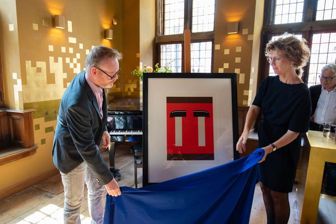 Het is al een tijd een wens van het Stedelijk Museum Kampen: een werk van geboren IJsselmuidenaar Jan Roeland in de collectie. Dankzij een genereuze gift van Richard Boddeus (links) wordt deze wens nu werkelijkheid. Hij schenkt de zeefdruk 'Compositie met twee hamers' aan het museum.