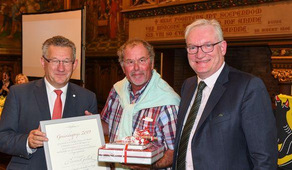 Burgemeester Dirk De fauw en raadslid Pol Van Den Driessche reiken de prijs uit aan de uitbater.