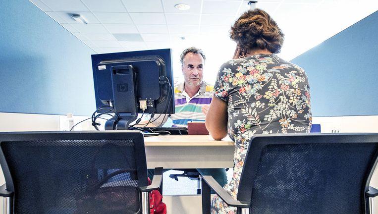 Bij het UWV in Haarlem praat een arbeidsbemiddelaar met een vrouw die na zeven jaar dienstverband haar betrekking is kwijtgeraakt Beeld Guus Dubbelman / de Volkskrant