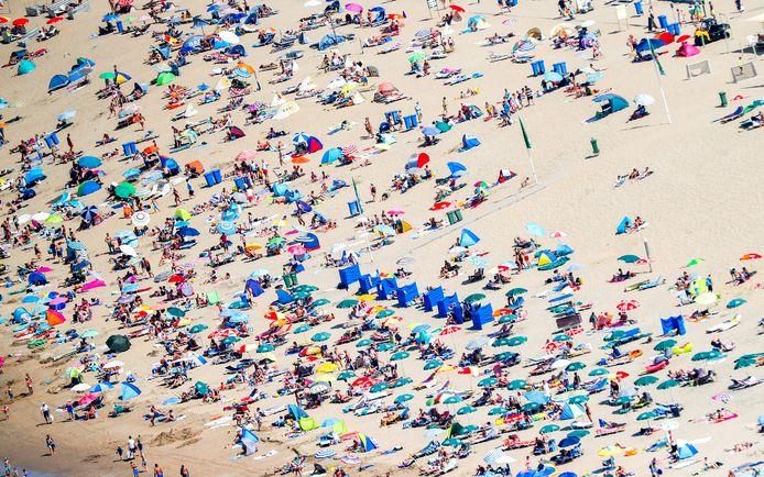 Mensen zoeken verkoeling op het strand. De foto is gemaakt voor de coronacrisis uitbrak.