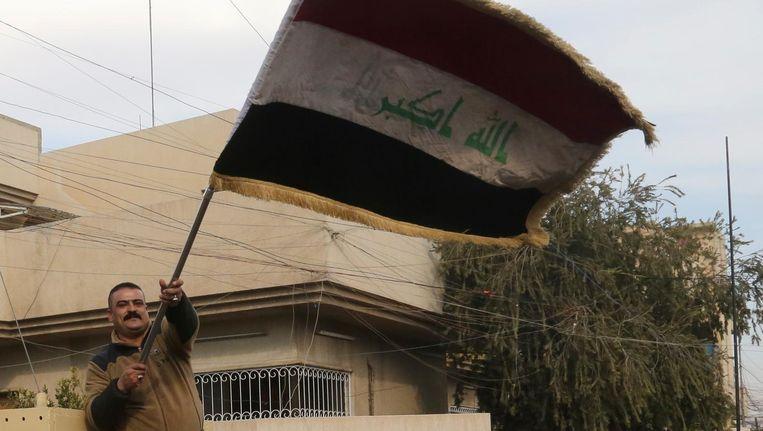 Een Iraakse soldaat zwaait met de Iraakse vlag in het oosten van Mosoel Beeld ap