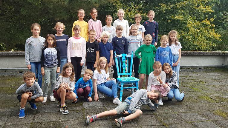 Een deel van de kinderklimaatambassadeurs bij een 'toekomststoel'.