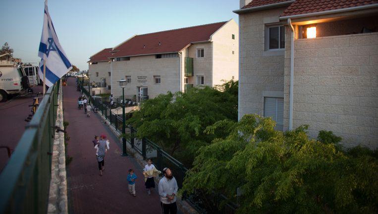 Inwoners van Ulpana wandelen door hun omstreden wijk. Beeld getty