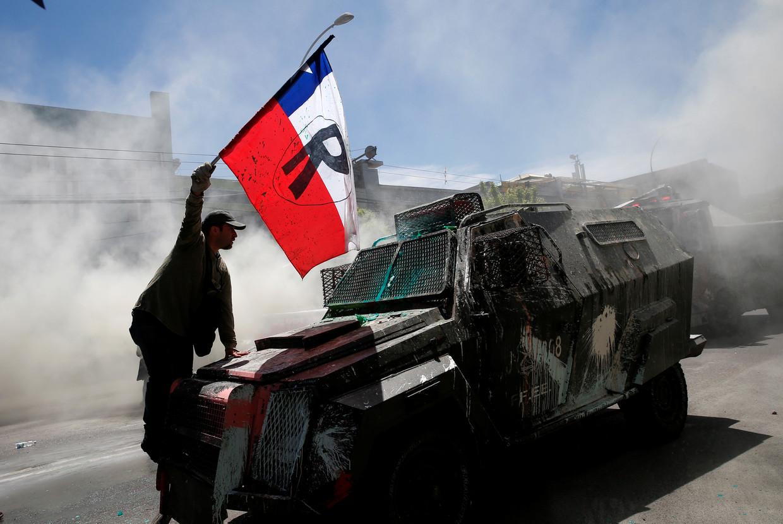 Een demonstrant beklimt een politievoertuig in Valparaiso, Chili.  Beeld REUTERS