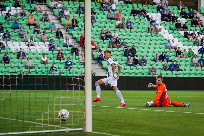 Op anderhalve meter afstand van elkaar kijken fans toe hoe Kian Slor van FC Groningen scoort, doelman Michael Brouwer van Heracles heeft het nakijken.