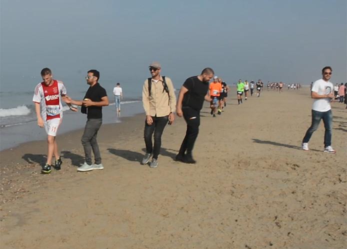 Lennart Reijnierse (in Ajax-shirt) wordt op het strand van Oostkapelle aangemoedigd door zijn vrienden. Hij finisht uiteindelijk in een tijd van 4 uur, 55 minuten en 44 seconden.