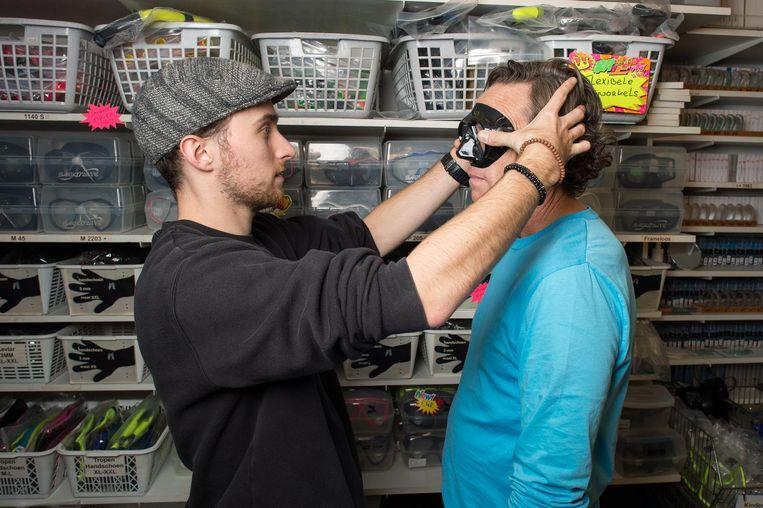 Medewerker Daan past een klant een nieuwe bril aan Beeld Mats van Soolingen