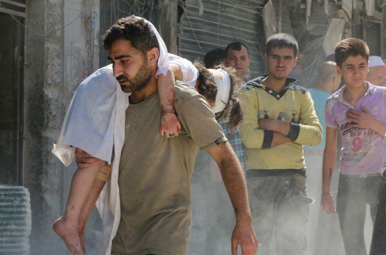 Een man draagt een gewond kind weg na de ontploffing van wat vermoedelijk een vatenbom was.