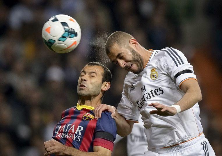 Benzema torent boven Barcelona-speler Mascherano uit en kopt de 1-0 binnen Beeld afp