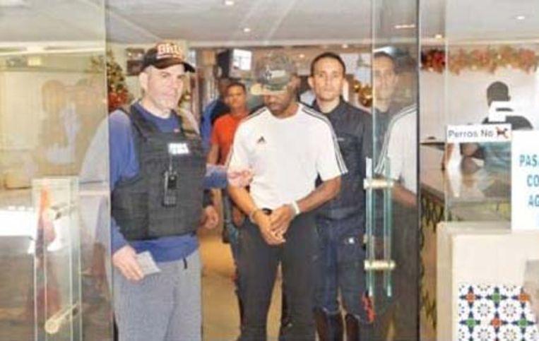 Speurders leiden Bombile L. uit hotel Santiago, waar hij zich schuilhield.