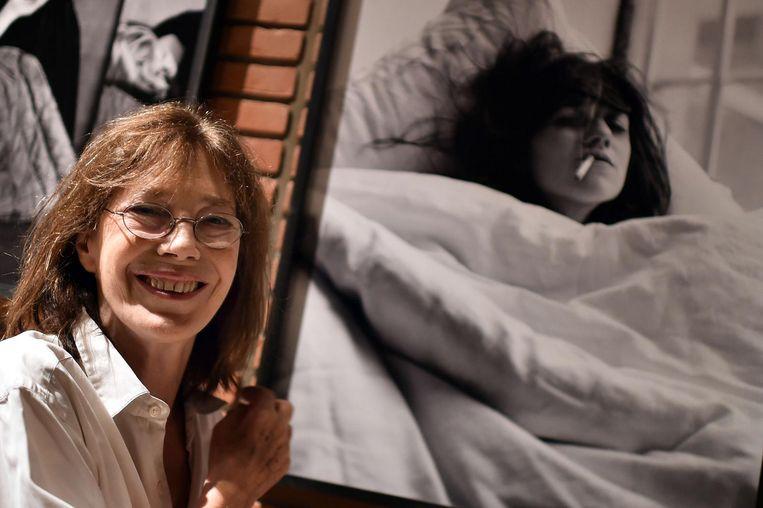 Jane Birkin poseert naast een foto van Charlotte Gainsbourg, als onderdeel van haar expositie