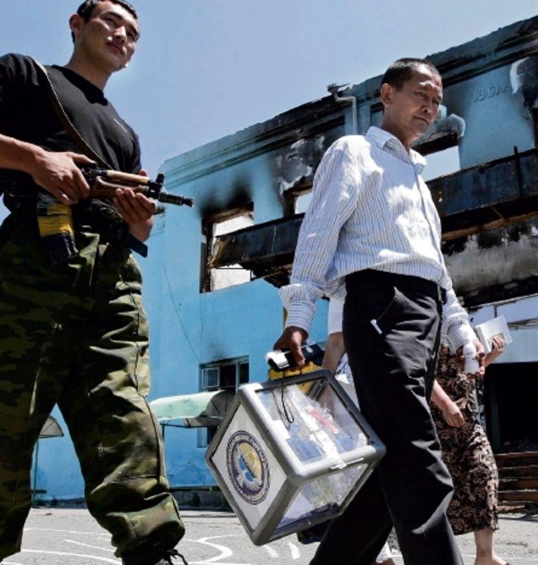 Een lid van het referendumcomité in Osj draagt ' onder zware bewaking ' de stembus. (FOTO EPA) Beeld