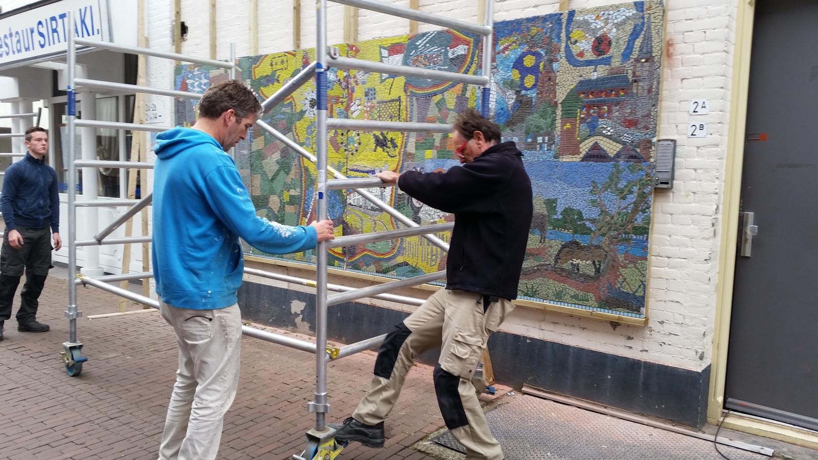 De panelen worden op de muur bevestigd. Vooraan (blauwe trui) kunstenaar en initiatiefnemer Alex van der Heijden.
