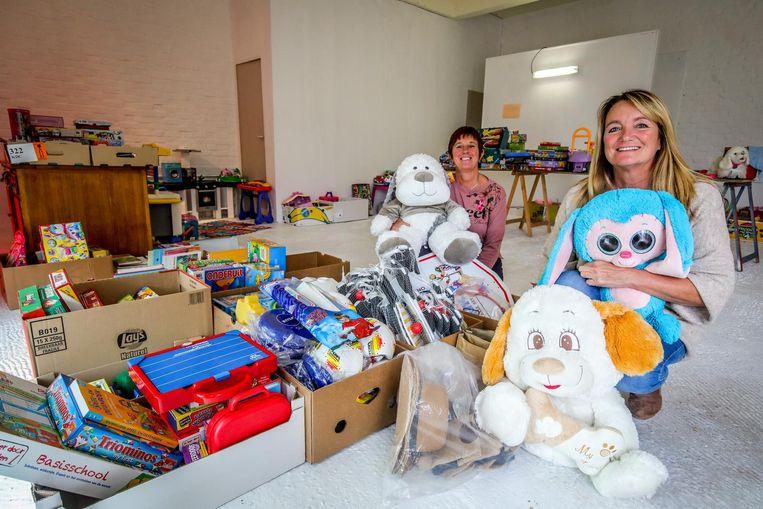 Katrien Lefever en Veronique Landuyt bij de dozen vol gezelschapsspellen, knuffels en ander speelgoed.