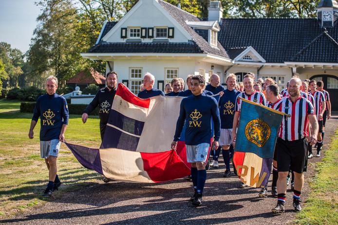 De spelers lopen met de traditionele vaandels van het Koetshuis naar het veld.