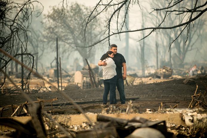 Gabriel Castillo en zijn vrouw Alea Kelleher kijken naar de ravage die de bosbrand bij hun huis in Santa Rosa in California heeft aangericht. De twee moesten maandag samen met hun 13 maanden oude dochter hun huis ontvluchten. Foto Noah Berger/Photonews