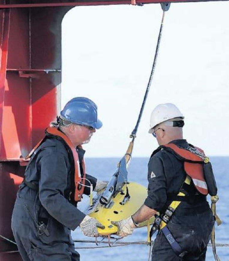 Bemanningsleden van het Australische schip met het apparaat dat zwarte dozen kan opsporen. Beeld epa