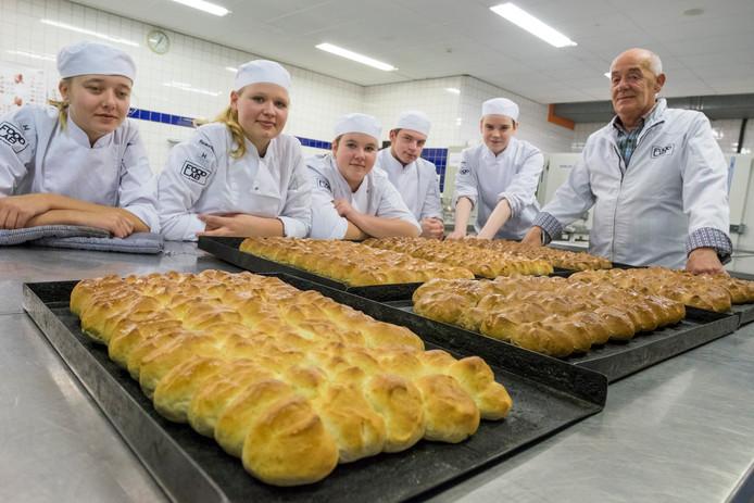 Ad Remijn (rechts) bakte hubkes met zijn leerlingen.