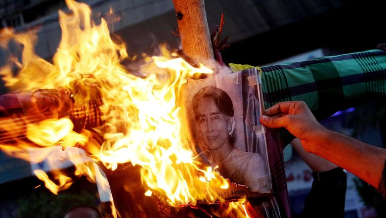Demonstranten steken een foto van Suu Kyi in brand. Beeld afp