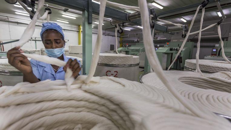 Een Ethiopische vrouw controleert het machinaal spinnen van katoen. Beeld null