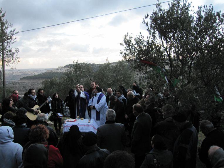 Eucharistieviering van kom-en-zie-pelgrims met christelijk-Palestijnse boeren in de Cremisanvallei. Beeld Gied ten Berge