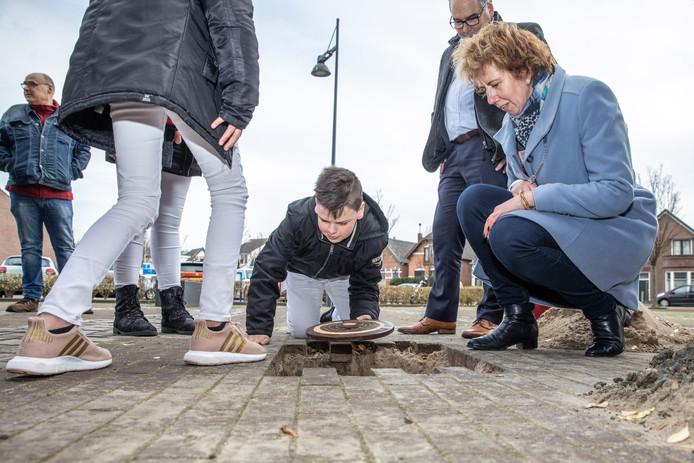 Kinderwethouder Jelmer van Mosselvelde legt het kleitablet onder de grond onder toeziend oog van burgemeester Margo Mulder.