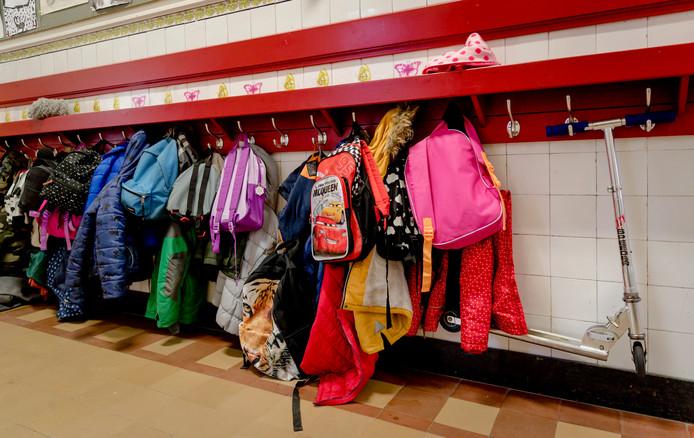 Een met tassen en jassen aan een kapstok op een basisschool.