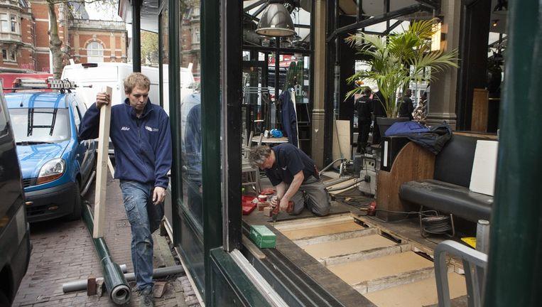 Timmermannen plaatsen een nieuwe vloer in de Heineken Hoek, waar zondag door vuurwerk brand ontstond. Beeld Floris Lok