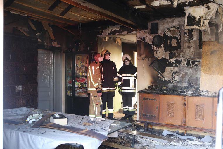 Brandweermannen inspecteren na het blussen de woning.