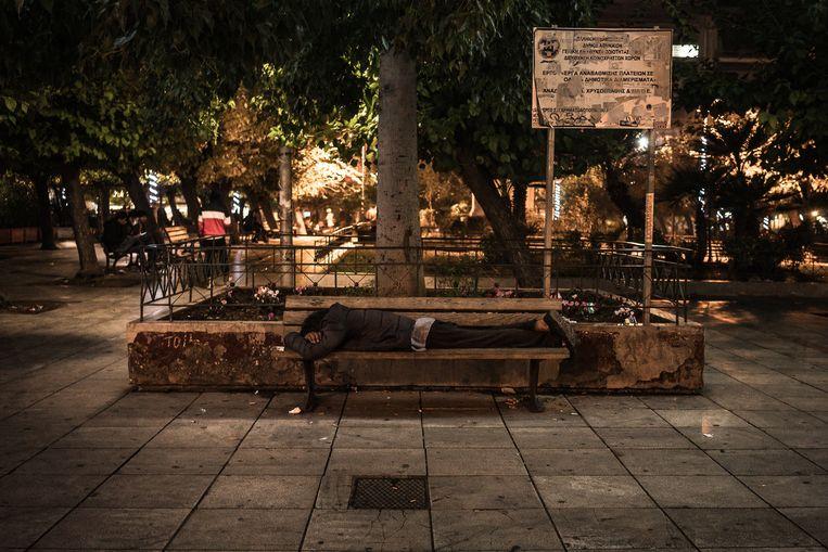 Een migrant brengt de nacht door op Victoria-plein in het centrum van Athene.  Beeld Nicola Zolin