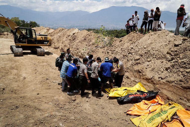 De eerste lichamen worden in een massagraf begraven op Sulawesi.