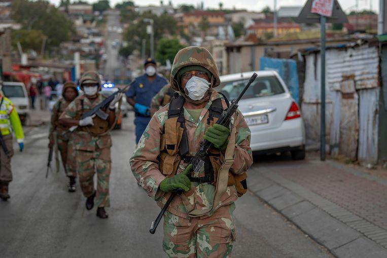 Zuid-Afrikaanse militairen patrouilleren in Alexandra, een arme wijk bij Johannesburg, om de voor drie weken afgekondigde lockdown af te dwingen. Veel arme Zuid-Afrikanen houden zich er niet aan. Beeld AP