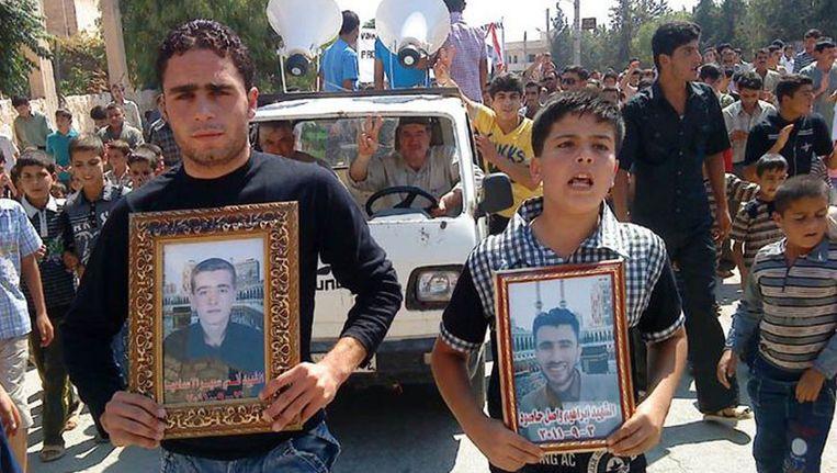 Twee demonstranten laten foto's zien van hun omgekomen familieleden tijdens een demonstratie in Homs. Beeld ap