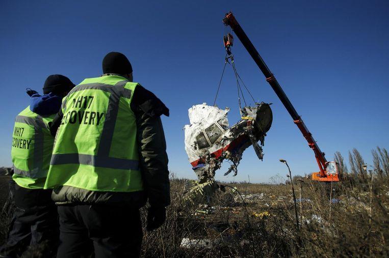 Een deel van de cockpit van vlucht MH17 wordt geborgen in Oost-Oekraïne, terwijl bergers toekijken. Beeld reuters