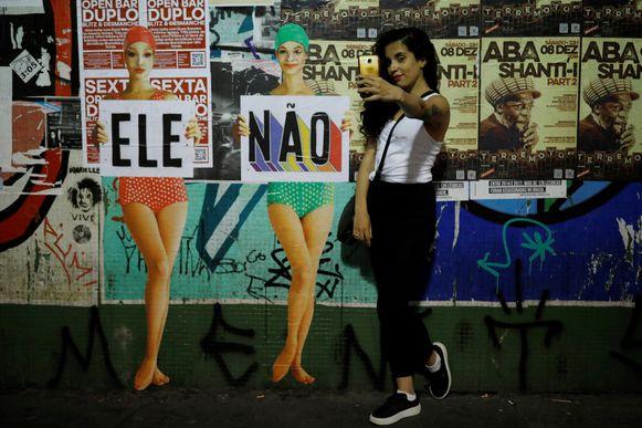 Een vrouw neemt een selfie bij een bord waarop de tekst 'hij niet' staat.