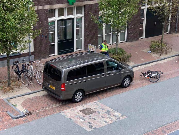 Een toezichthouder deelt een waarschuwing uit aan de bestuurder van een rouwauto in Zwolle. De wagen stond geparkeerd bij het Theodora Vos De Wael Huis vanwege een overleden cliënt.