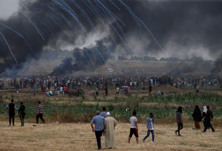 De Israëlische troepen vuren traangas over het rookgordijn van de Palestijnse betogers heen.