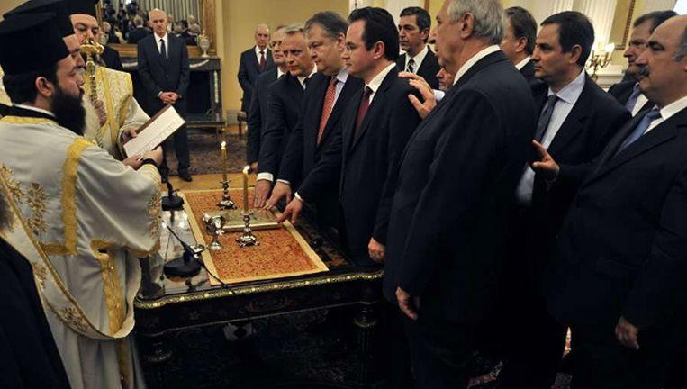 De aartsbisschop van de Grieks-orthodoxe kerk zweert leden van de Griekse regering in. Minister Venizelos van financiën staat in het midden achter de tafel. ©AFP Beeld