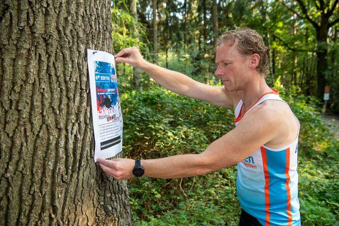 Hardloper Albert Mussche, voorzitter van Loopgroep AG '85 uit Nieuwleusen/Staphorst hangt een affiche van de Vechtdal Crosscompetitie op bij de Zwarte Dennen. Ondanks corona gaan de vier organiserende clubs voor de zesde jaargang van dit crosscircuit.