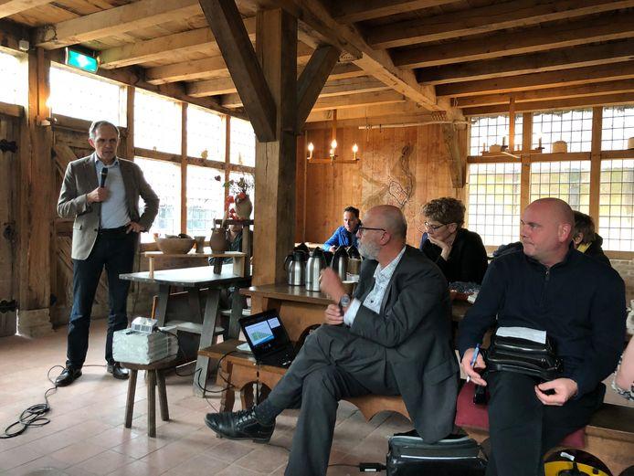Voorzitter Henk Gernand (midden) van de huurdersvertegenwoordiging van corporatie Woonbedrijf luistert naar Paulus Janssen van de Woonbond op de Huurdersmanifestatie Aardgasvrij , in de herberg van het Prehistorisch Dorp in Eindhoven.