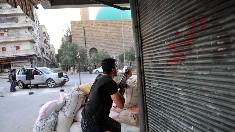 Een Syrische rebel kiest positie in Aleppo, de tweede stad van Syrië. Beeld AFP