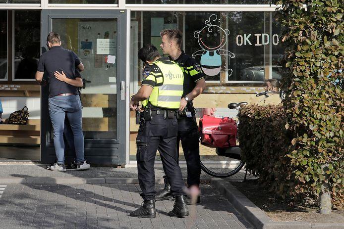 Politie bij Okido aan de Obrechtstraat waar mensen bijeenkomen na het ongeluk bij station Oss West.