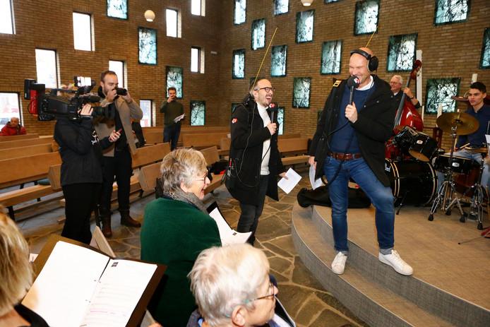 Radiopresentatoren Frank van 't Hof en Wouter van der Goes (rechts) hebben lol met het kerkkoor uit Leerdam.