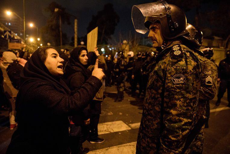 Een vrouw praat tegen een politieagent tijdens een herdenking van de slachtoffers van het Oekraïens passagierstoestel. Beeld AFP