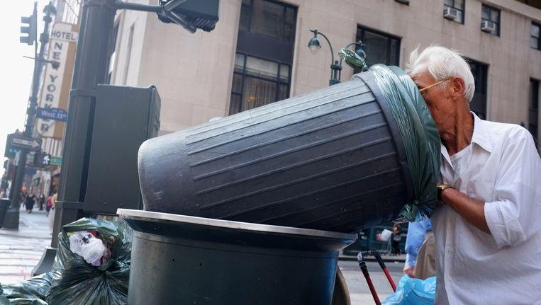 Een man in New York zoekt tussen het afval. Beeld AFP